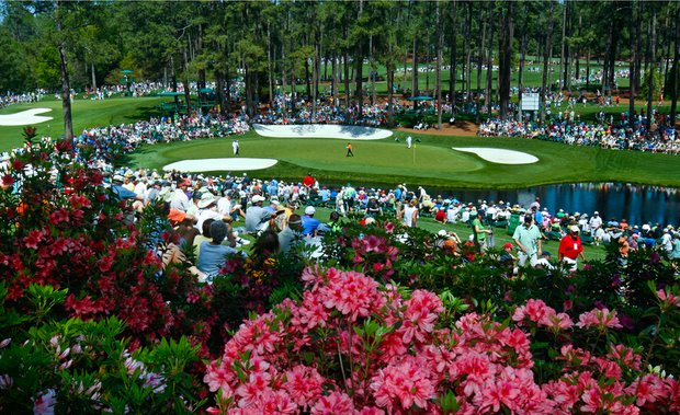 Fans wait around the par-3 16th hole at Augusta National during Monday's practice round.