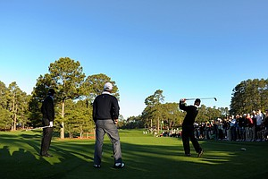 Kevin Streelman hits a shot as Phil Mickelson and Fred Couples look on during a practice round for the Masters.