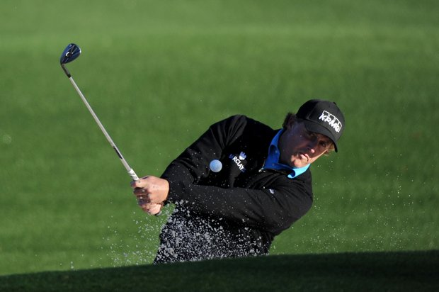 Phil Mickelson plays a practice shot out of a bunker at Augusta National.