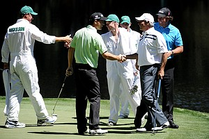 On the eve of the Masters, Padraig Harrington shakes hands with Fred Couples as Phil Mickelson looks on.