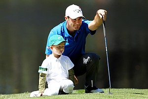 Trevor Immelman of South Africa waits with his son Jacob on a green during the Masters Par 3 Contest.