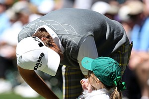 Aaron Baddeley of Australia chats with his daughter Jewell during the Masters Par 3 Contest.