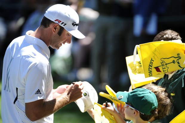 Dustin Johnson signs autographs during the Masters Par 3 Contest.
