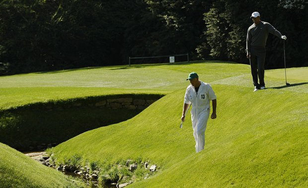 Tiger Wood's caddie Steve Williams retrieves a ball from the creek on the 13th green during a practice round prior to the 2011 Masters.