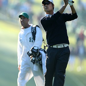 Kevin Na watches a shot on the first hole as his caddie Kenny Harms looks on during the first round of the 2011 Masters Tournament at Augusta National Golf Club on April 7, 2011 in Augusta, Georgia.