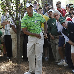 Tiger Woods of the US looks after a shot from near a tree on the third hole during the first round of the Masters golf tournament at Augusta National Golf Club on April 7, 2011 in Augusta, Georgia.