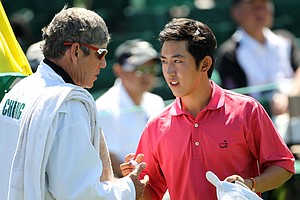 Amateur David Chung shakes hands with his caddie Adam Schriber on the 18th green during the first round of the 2011 Masters Tournament at Augusta National Golf Club on April 7, 2011 in Augusta, Georgia.
