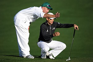 Camilo Villegas of Colombia lines up a putt with the help of his caddie Mick Doran on the second hole during the first round of the 2011 Masters Tournament at Augusta National Golf Club on April 7, 2011 in Augusta, Georgia.