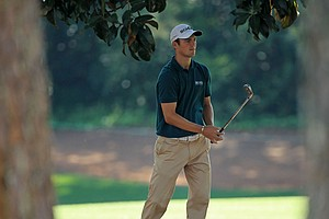 Martin Kaymer hits a shot from the pine needles on the 18th hole during the first round of the 2011 Masters.