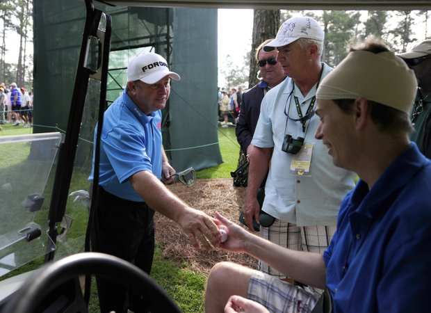 Ian Woosnam of Wales gives a golf ball to fan Mathew Long after hitting him with a shot on the 6th hole during the second round of the Masters golf tournament at Augusta National Golf Club on April 8, 2011 in Augusta, Georgia.