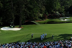 Rory McIlroy hits his tee shot on the 12th hole while caddie J.P. Fitzgerald, Jason Day and caddie Colin Swatton look on during the third round of the 2011 Masters.