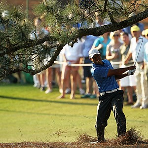 Tiger Woods hits a shot from the pine needles on the 17th hole during the third round of the 2011 Masters.