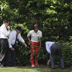 Ryo Ishikawa of Japan talks to rules officials about his shot in the bushes off the fourth hole during the final round of the Masters golf tournament Sunday, April 10, 2011, in Augusta, Ga.