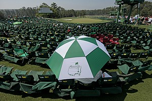 Larry Robers, from Nashville, Tenn., shades himself from the sun while waiting for play at the 18th green during the final round of the Masters golf tournament Sunday, April 10, 2011, in Augusta, Ga.