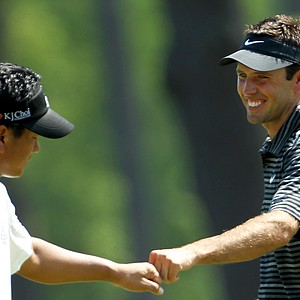 Charl Schwartzel of South Africa (R) celebrates with K.J. Choi of South Korea after Schwartzel holed a shot for eagle on the third green during the final round of the 2011 Masters Tournament on April 10, 2011 in Augusta, Georgia.