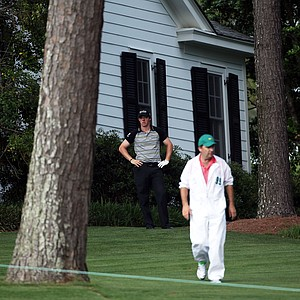 Rory McIlroy of Northern Ireland waits to plays a shot on the tenth hole as his caddie J.P. Fitzgerald looks on during the final round of the 2011 Masters Tournament at Augusta National Golf Club on April 10, 2011 in Augusta, Georgia.