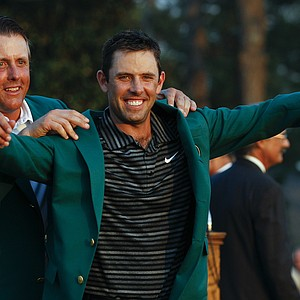 Former champion Phil Mickelson, back, helps Charl Schwartzel of South Africa with his green Masters jacket after winning the Masters golf tournament Sunday, April 10, 2011, in Augusta, Ga.