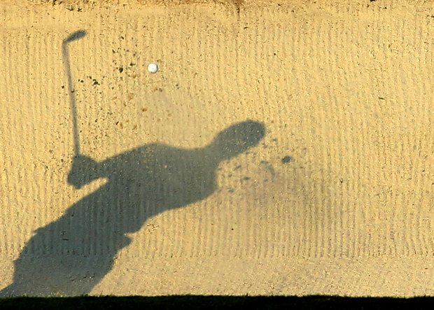 The shadow of Tiger Woods is seen as he hits from a bunker on the 17th hole during the third round of the 2011 Masters Tournament at Augusta National Golf Club on April 9, 2011 in Augusta, Georgia.