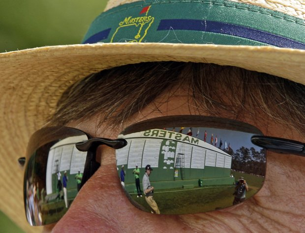 Rod Strader of Atlanta stands near the scoreboard near the first hole during the final round of the Masters golf tournament Sunday, April 10, 2011, in Augusta, Ga.