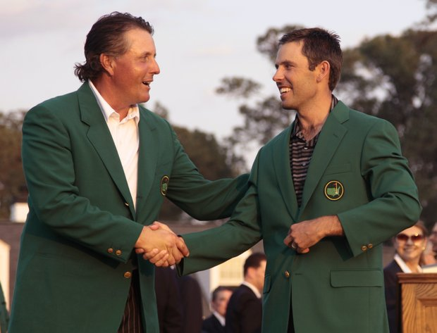 Former champion Phil Mickelson, left, shakes hands with Charl Schwartzel after Schwartzel won the 2011 Masters.