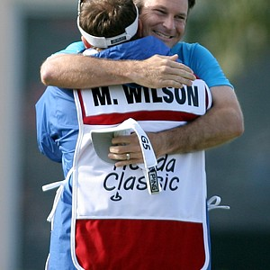 Mark Wilson, center, hugs his caddy Chris P. Jones, right, after defeating Jose Coceres, of Argentina, during the third playoff hole on the 17th hole at the Honda Classic golf tournament, Monday, March 5, 2007, in Palm Beach Gardens, Fla.