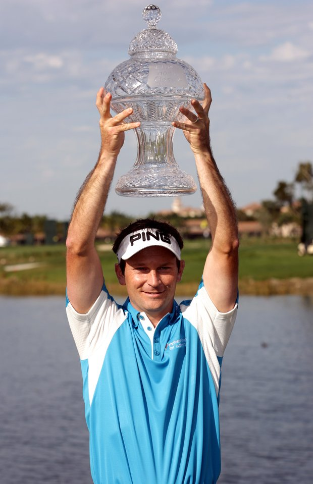 Mark Wilson holds up the trophy after after defeating Jose Coceres, of Argentina, during the third playoff hole on the 17th hole at the Honda Classic golf tournament, Monday, March 5, 2007, in Palm Beach Gardens, Fla.
