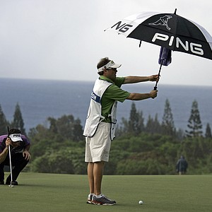 Mark Wilson, left, lines up his putt as his caddie keeps his ball dry on the ninth green of the Plantation Course during the first round of the Mercedes-Benz Championship golf tournament in Kapalua, Hawaii, Thursday, Jan. 3, 2008.