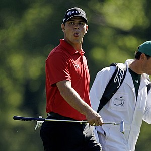 Gary Woodland reacts after hitting a shot on the 12th hole during a practice round for the Masters golf tournament Wednesday, April 6, 2011, in Augusta, Ga. At right is caddie Jon Yarbrough.