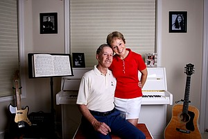 "Dave  and Nicole Ragaini pose in their music room in the home they share at Black Diamond Ranch. In 1998, Dave and Nicole recorded an album - ""Love Looks So Well On You."""
