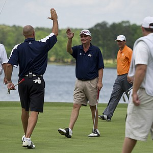 Jon Barry (left) high-fives Georgia Tech coach Paul Johnson after a birdie on No. 18 at the Chick-fil-A Bowl Challenge in Greensboro, Ga.