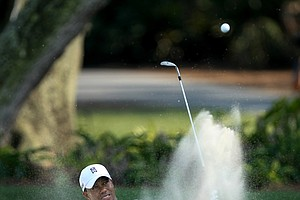 Tiger Woods hits out of a bunker at No. 9 during a Tuesday practice round at The Players Championship at TPC Sawgrass.-