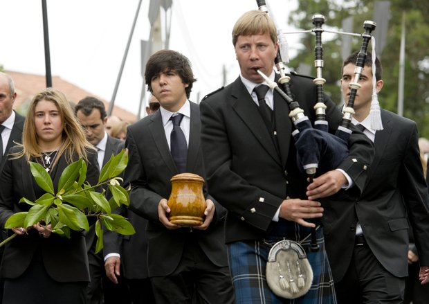 A bagpiper leads the funeral procession for Spanish golfer Seve Ballesteros, whose ashes are carried by oldest son Javier, with sister Carmen (left) and brother Miguel (right) joining the mourners Wednesday in Pedrena, Spain. Ballesteros, 54, a five-time major champion, died Saturday from complications of a cancerous brain tumor.