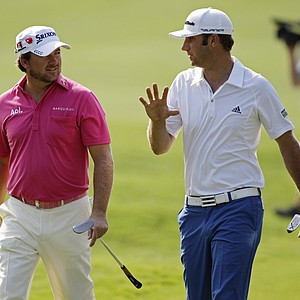 Dustin Johnson, right, and Graeme McDowell walk the fifth fairway during the first round of The Players Championship.