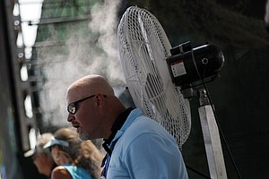 Brant Brice of Jacksonville, Fla. cools off from the heat during the first round of The Players Championship.
