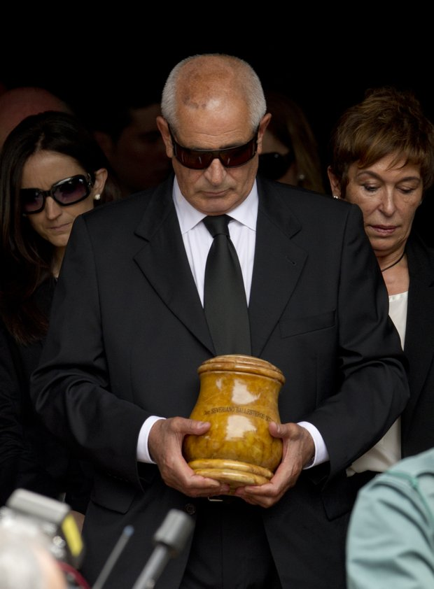 Baldomero Ballesteros, center, carries the urn holding the ashes of his brother, Spanish golfer Seve Ballesteros, during his funeral service in of Pedrena, Spain, Wednesday May 11, 2011.