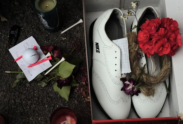 Candles and a red flower are seen beside golf shoes during the funeral service of Spanish professional golfer Seve Ballesteros, in Pedrena, Spain, Wednesday May 11, 2011.