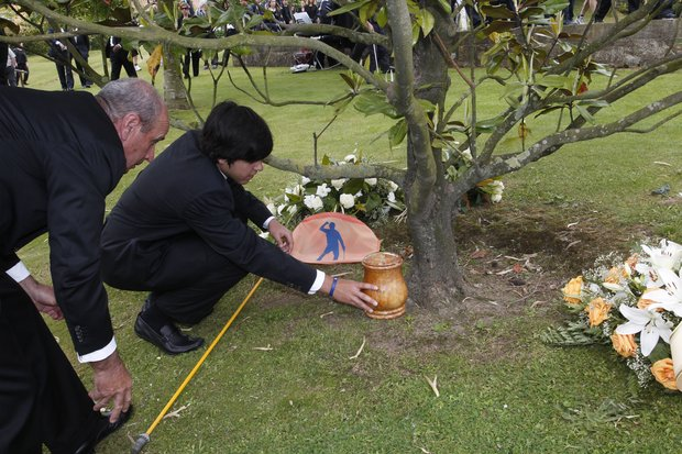 Javier Ballesteros places the urn containing the ashes of his father, Spanish golfer Seve Ballesteros, under the magnolia tree, on the premises of the family estate, at the end of the funeral service in Pedrena, Spain, Wednesday, May 11, 2011.