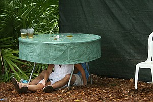 A couple seeks shelter underneath a table during a rain delay on Saturday.