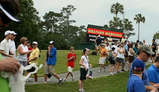 A digital scoreboard prepares fans for approaching bad weather during Round 3 of The Players Championship.