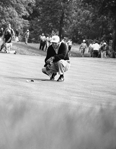Tommy Bolt lines up a putt on the 11th green during the U.S. Open at Winged Foot GC in Mamaroneck, N.Y., on June 11, 1959.