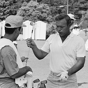 Arnold Palmer, one of golf's all time stars, lets out a big puff as he hands a club to his caddy during a practice round at the Champions Golf Club in Houston, Texas, on June 10, 1969 where the U.S. Open gets under way Thursday. High temperature and humidity made many of the contestants uncomfortable as they toured the 6,967-yard layout.