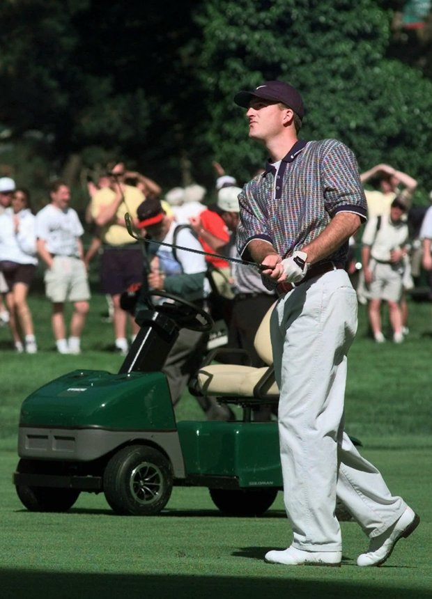 Casey Martin watches his shot on the 9th fairway during a practice day of the 1998 U.S. Open Championship on the Lake Course of the Olympic Club in San Francisco, Calif., Tuesday, June 16, 1998. Martin's cart, used because of a circulatory disorder in his right leg, is in the background.