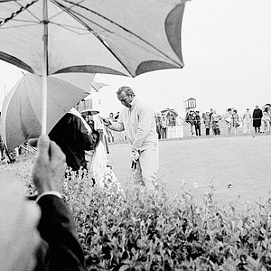 Arnold Palmer, right, is assisted by his caddy as he dries off his clubs while waiting to off in third round of play in U.S. Open tournament in Chaska, Minnesota on Saturday, June 20, 1970. Palmer began his third round twelve strokes off pace with a 153 for the first two rounds.
