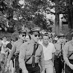 Arnold Palmer is surrounded by a quartet of New Jersey State Police as he is escorted to the press tent for an interview, June 16, 1967 at Springfield, N.J. He had just posted a 68 in today's second round of the U.S. Open Golf Championship to lead the field at the end of two days with 137 score.