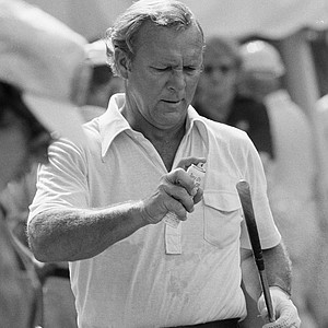 Arnold Palmer of Ligonier, Pa. concentrates on spraying the grip of a golf club before warming up in a practice round at Medinah Country Club, June 18, 1975. Palmer, who has played golf with presidents and monarchs all over the world, takes care of this chore himself preparing for the U.S. Open, which gets underway at Medinah Thursday.
