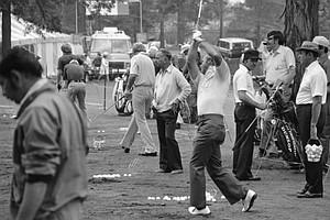 While Arnold Palmer, center, hits from the practice tee at Medinah Country Club, Tuesday, June 17, 1975, Medinah, Ill. Gary Player of South Africa, dark cap, and veteran Sam Sneed, holding a bucked of ball at right, await their turn to get in some swings in preparation for the U.S. Open Tournament. Practice was on-again off-again as rains plagued the course all day.