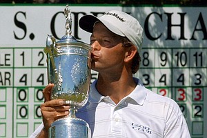 Retief Goosen, right, of South Africa, kisses the winner's trophy on the 18th green at Southern Hills Country Club after beating Mark Brooks in a 18-hole playoff for the U.S. Open Championship, Monday, June 18, 2001, in Tulsa, Okla.