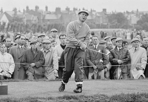 Bundled against the cold and rain defending champion Arnold Palmer tees off on the short fifth hole in the first round of the British Amateur open golf championship at St. Anne's, England, July 10, 1963.