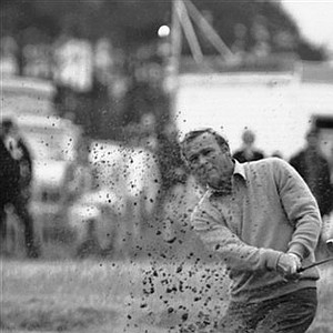 Arnold Palmer is covered by sand as he hits out of a bunker on the 6th hole in the 1975 British Open in Carnoustie, Scotland.