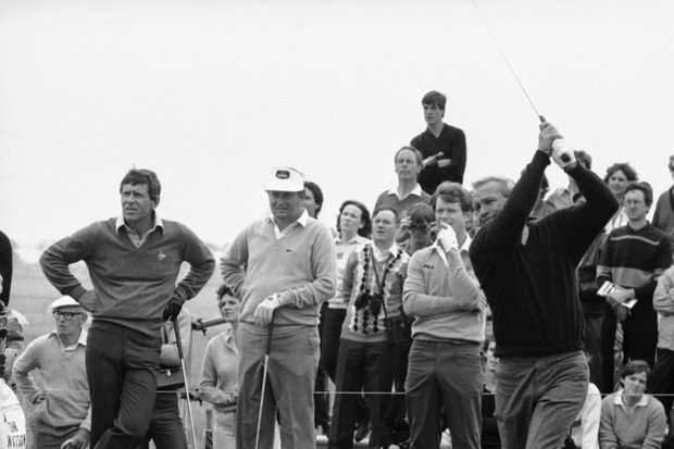 Veteran American golfer Arnold Palmer, right, is watched closely by Tom Watson, second from right, holder of the U.S. Open title, as he drives off during practice before the start of the Open Golf Championship, July 14, 1982, Troon, Scotland.